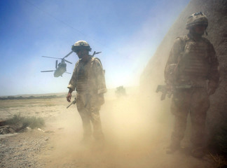 Dust billows as a British Chinook helicopter takes off in Sangin valley
