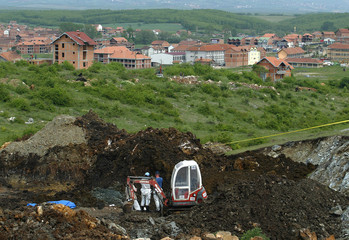 Forensic experts dig a mass grave where bodies of presumed Serbs have been found in the Kosova ...