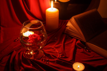 night red still life with candles, a rose, a book and a record