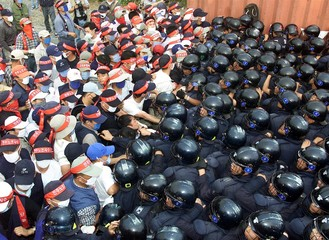 Unionised workers (L) from South Korea's Hyosung Corp scuffle with riot police blocking their march ..