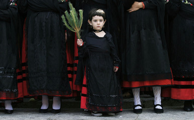 "A young girl dressed as a ""pinorra"" carries a pine branch during the Pinochada festival in the northern Spanish village of Vinuesa"