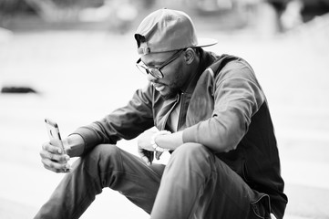 Portrait of stylish african american man on sportswear, cap and glasses sitting on stairs with phone at hand. Black men model street fashion.