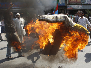 Students from Islami Jamiat-e-Talba group burn an effigy representing Denmark during a protest in Karachi