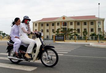 Vietnamese school girls ride their bike past the communist People's Court in Vung Tau, Vietnam