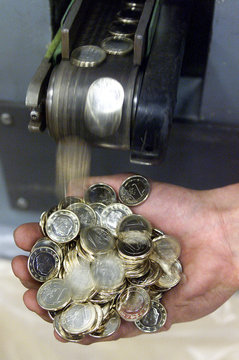 An employee at Belgium's Royal Mint collects one euro coins as they leave the minting press in Bruss..