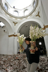 Bolivian rescues flower vases after the dome and roof of historic church collapsed in La Paz