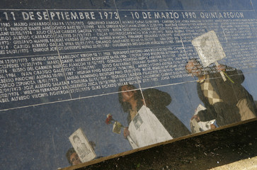 Demonstrators are reflected in monument to detained and disappeared people, during rally in Valparaiso City