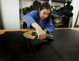 A Colombian worker uses a tool to cut out a piece of leather in Bogota