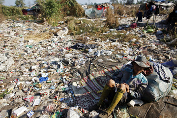An illegal immigrant from Myanmar rests from collecting plastic at a rubbish dump site near Mae Sot