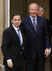 Brice Hortefeux, France's newly-named Labour and Socials Affairs Minister, welcomes his successor Eric Besson, newly-named Immigration Minister, outside the ministry in Paris