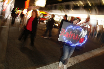 """A fan holding a sign that reads """" Rain's"""" walks after the premiere of the movie """"Ninja Assassin"""" at the Grauman's Chinese Theatre in Hollywood"""