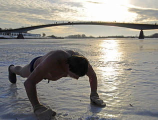 A man exercises before swimming in the River Vokhov in Russia's ancient city of Veliky Novgorod