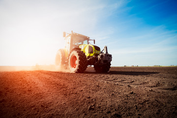 Tractor working on farm land on sunset