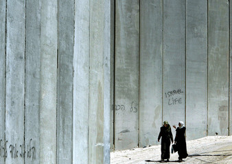 Two Palestinian women walk in front of a concrete wall which separates the eastern neighbourhoods of ...