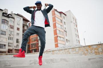 Portrait of jumping stylish african american man on sportswear, cap and glasses. Black men emotion model street fashion.