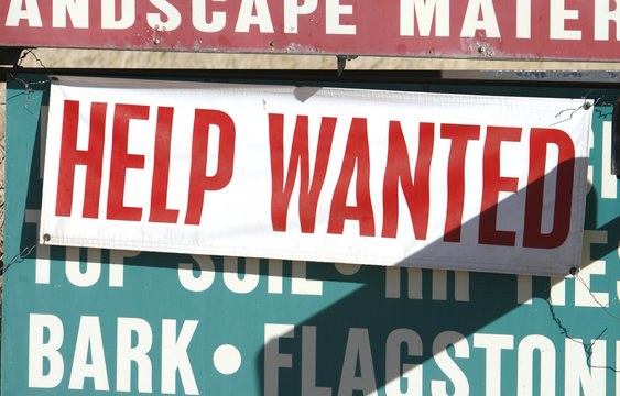 A sign at a landscape supply company advertises available jobs in Arvada