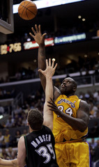 LAKERS SHAQUILLE ONEAL SHOOTS OVER TIMBERWOLVES MARK MADSEN IN NBA PLAYOFF GAME 4.
