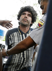 Cuban Punk rocker Gorki Aguila is escorted by police to court in Havana