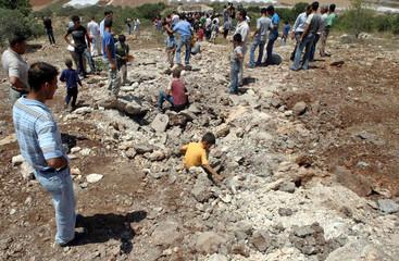 Palestinians survey the scene after a Hizbollah rocket landed near Jenin