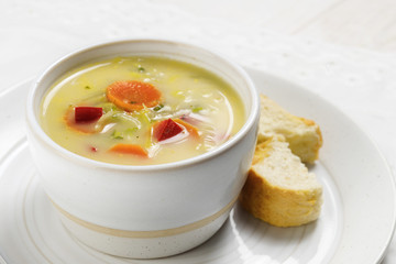 soup with healthy vegetables like carrot, red pepper and leek in a bright ceramic bowl with bread on a plate, white table, close up