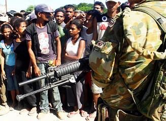 Australian troop guards East Timorese people as they queue for rice in the capital Dili