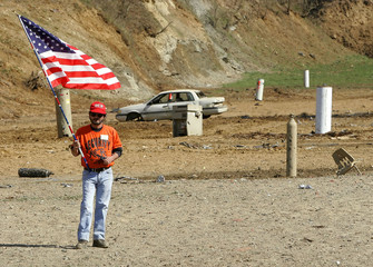 Man stands with American flag during national anthem at machine gun shoot.
