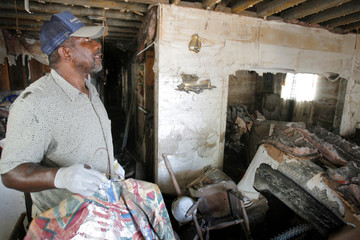 Larry Williams looks at what used to be the living room of his friend Patricia Miller's home in New Orleans