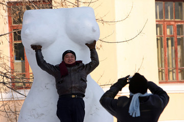 Chinese man takes picture of his friend in front of human-body sculpture in park in Harbin