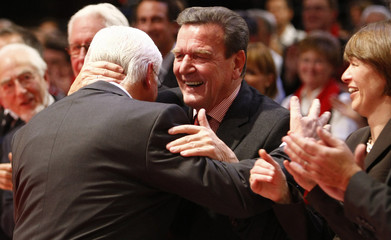 German Foreign Minister Steinmeier is embraced by former German Chancellor Schroeder during SPD party convention in Berlin