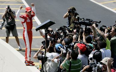 Ferrari's Formula One driver Felipe Massa of Brazil celebrates in the pits after qualifying first for the pole position at the Interlagos racetrack in Sao Paulo