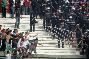 Fans of JSM Bejaia clash with riot police during the Algeria Cup final soccer match in Blida stadium