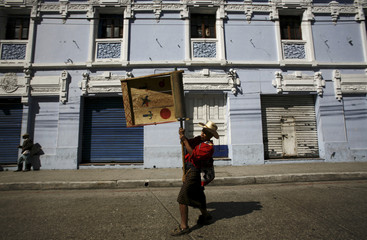 A Mayan Indian carries a giant, hand-made noise maker during a march welcoming President Alvaro Colom's new government in Guatemala City