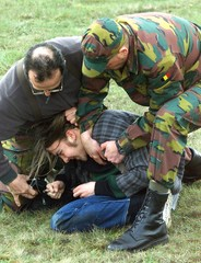 TWO BELGIAN SOLDIERS ARREST A PEACE ACTIVISTS AS HE TRIES TO ENTER THE BELGIAN NATO AIR BASE IN ...