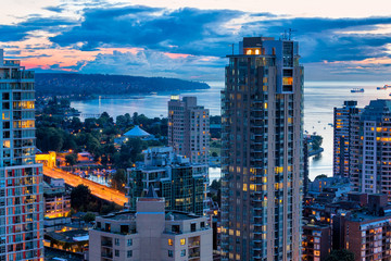 Vancouver Canada aerial city view at colorful sunset. Illuminated skyscrapers and the bay is shown in the background Fototapete