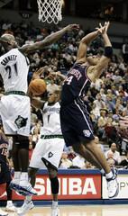 Nets Jefferson has shot blocked by Timberwolves Garnett and McCants in Minneapolis