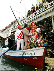 Peruvian believers throw flowers to religious icon of Saint Peter from bridge in Lima.