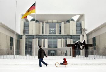 A man pulls a child on a sledge through the snow in front of the federal Chancellery in Berlin in th..