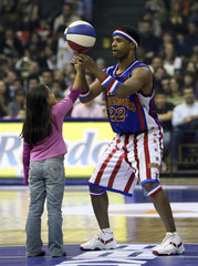 Herbert Lang of Harlem Globetrotters helps a Turkish girl to balance ball during exhibition game with NY Nationals in Istanbul