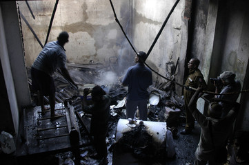 Staff attempt to extinguish small fires at Leader Publications' burnt-down printing press in Colombo