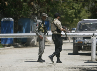 An Afghan policeman and a security guard stand in front of the Danish embassy in Kabul