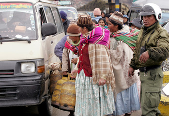 Bolivians from El Alto protest with domestic gas canisters while they block a hightway in La Paz