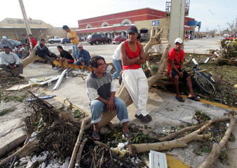 Residents wait on fallen tree after Hurricane Wilma hit at the Mexican Caribbean island of Cozumel