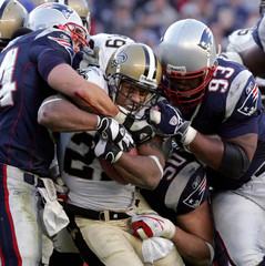 Saints Stecker is taken down by Patriots Bruschi and Patriots Seymour during the fourth quarter of NFL action in Foxboro
