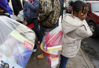 A child waits to cross the street with her bag of toys and winter clothes in Brooklyn