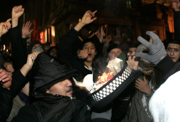 Pro-Palestinian demonstrators set fire to a policeman's hat during a protest near the Israeli embassy in London