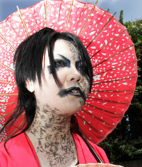 A Japanese girl with her face written with various Japanese kanji characters stands under parasol in Tokyo.