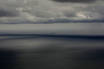 A boat sails by the Mediterranean Sea under a rain storm in front of the beach of Castelldefels near Barcelona