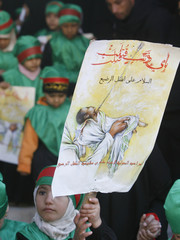 A girl holds up a picture of a baby, symbolising the son of Imam Hussein who was killed in Ashura, at Imam Hussein shrine in Kerbala