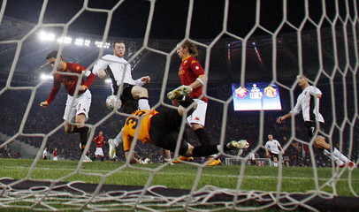 Manchester United's Rooney manoeuvres to score past AS Roma goalkeeper Doni during their Champions League quarter-final, first leg soccer match at the Olympic stadium in Rome