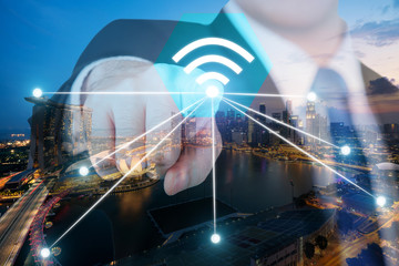 Businessman push wifi icon on city and network connection concept. Singapore smart city and wireless communication network, abstract image visual, internet of things.
